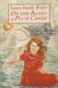 on the banks of plum creek laura ingalls wilder cover art book stack
